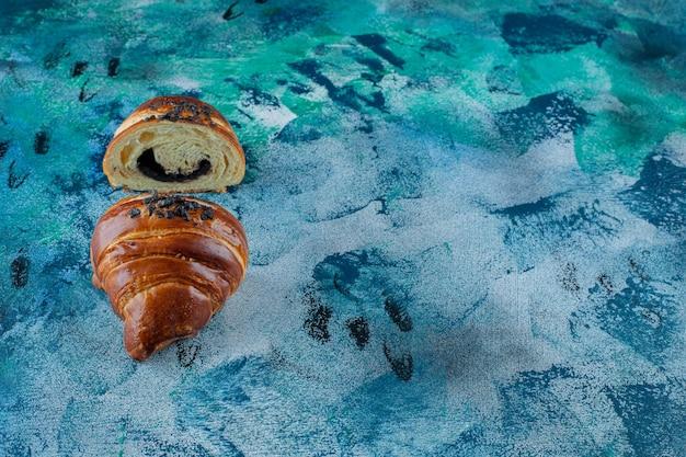 Hausgemachtes, in scheiben geschnittenes croissant mit schokolade, auf dem marmortisch.