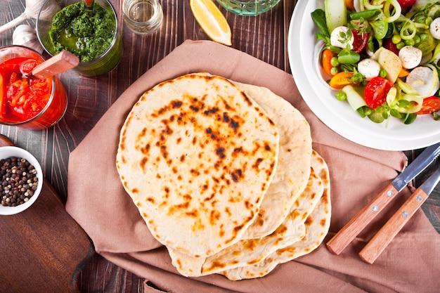 Hausgemachtes indisches naan-fladenbrot mit frischem salat und dips auf dem esstisch