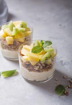 Hausgemachtes joghurtparfait mit müsli, kiwi, ananas und nüssen in einem glas für gesundes frühstück auf betonhintergrund