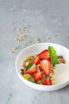 Hausgemachtes knuspriges müsli mit nüssen, getrockneten früchten, frischen erdbeeren, minze und joghurt (fermentierte gebackene milch)