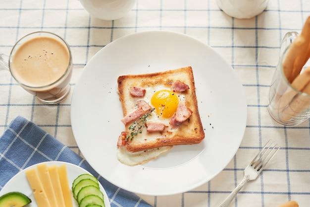 Hausgemachtes köstliches amerikanisches frühstück mit spiegelei, toast, wurst von der sonnenseite nach oben. englisches frühstück mit spiegeleiern, speck, würstchen und toast. frühstück am valentinstag. guten morgen konzept.