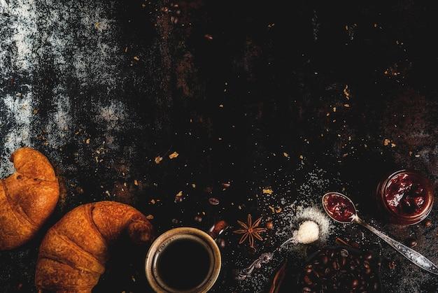 Hausgemachtes kontinentales frühstück, kaffee mit gewürzen, rohrzucker, croissants. stau auf einer schwarzen rostigen metalltabelle, copyspace draufsicht