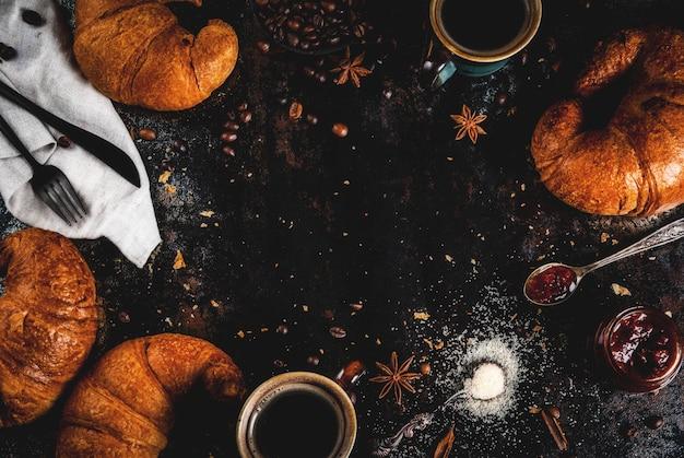 Hausgemachtes kontinentales frühstück, kaffee mit gewürzen, rohrzucker, croissants. stau auf einer schwarzen rostigen metalltabelle, copyspace draufsichtrahmen