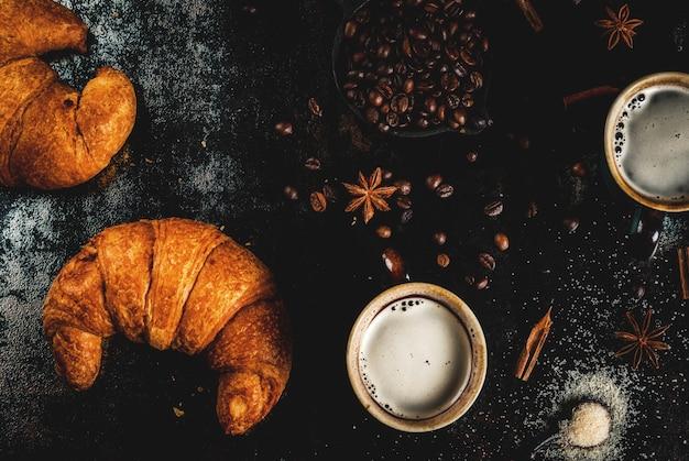 Hausgemachtes kontinentales frühstück, kaffee mit gewürzen, rohrzucker, croissants. stau auf einer schwarzen rostigen metalltabelle, draufsicht copyspace