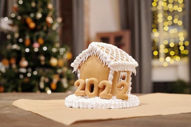 Hausgemachtes lebkuchenhaus dekoriert mit schlagsahne und gebackenen nummern des nächsten jahres