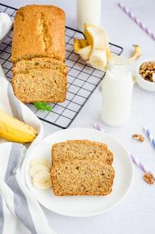 Hausgemachtes leckeres bananenbrot mit nüssen und zimt auf einem weißen teller mit einer flasche milch und frischen bananen. vertikale ausrichtung.
