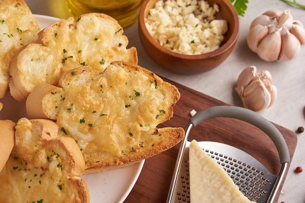 Hausgemachtes leckeres brot mit knoblauch, käse und kräutern auf dem küchentisch.