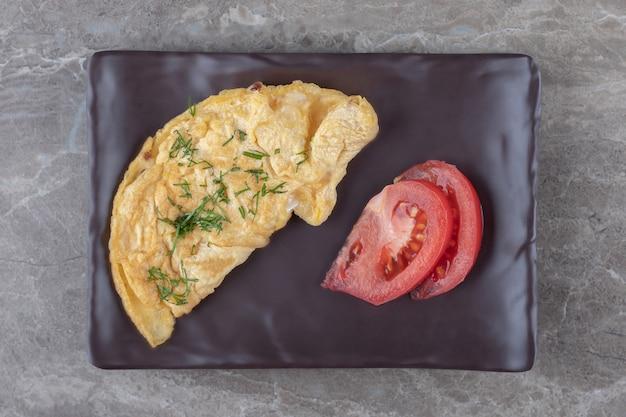 Hausgemachtes leckeres omelett mit tomate auf dunklem teller.