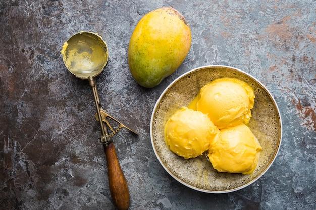 Hausgemachtes mango-eis in schalen mit frischen früchten über dunkelgrau
