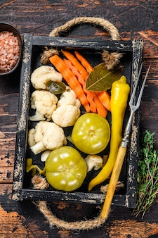 Hausgemachtes mariniertes und eingelegtes gemüse auf einem holztablett aufbewahren
