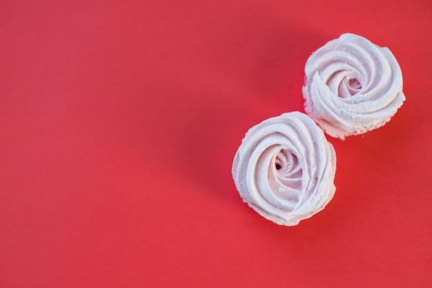 Hausgemachtes marshmallowrosa. schwarze johannisbeere, heidelbeer-marshmallows. zuckerkekse. pastellfarbener hausgemachter zephyr oder marshmallow isoliert auf rot. handgemachtes gebäckkonzept. kopierraum