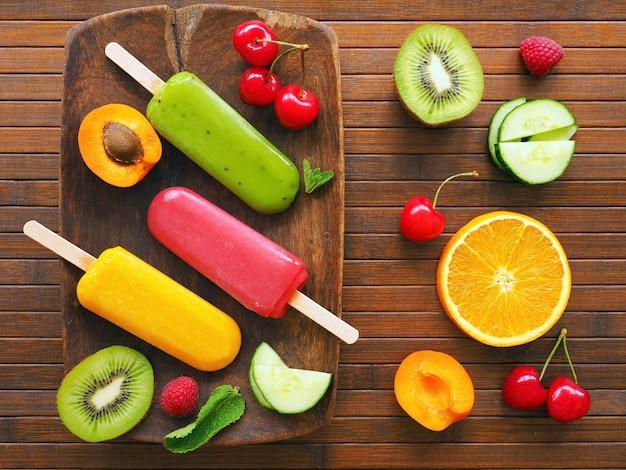 Hausgemachtes mehrfarbiges sorbet mit früchten auf holzoberfläche