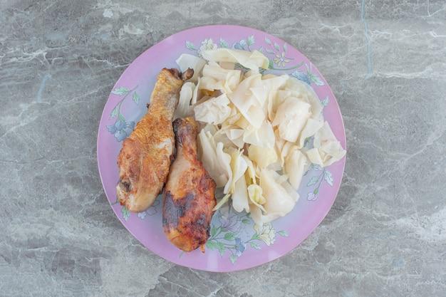 Hausgemachtes mittagessen. gegrillte hähnchenkeulen und kohlgurke.