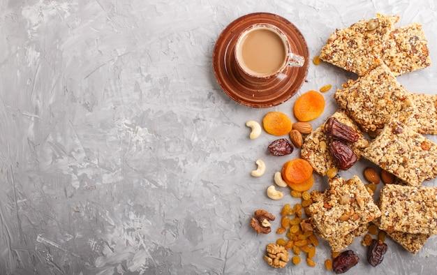 Hausgemachtes müsli aus haferflocken, datteln, getrockneten aprikosen, rosinen, nüssen mit einer tasse kaffee. ansicht von oben.
