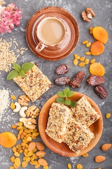 Hausgemachtes müsli aus haferflocken, datteln, getrockneten aprikosen, rosinen, nüssen mit einer tasse kaffee auf einer schwarzen betonoberfläche. draufsicht.