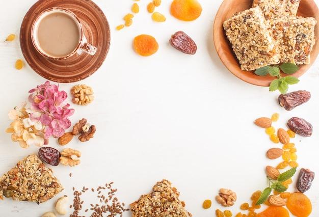 Hausgemachtes müsli aus haferflocken, datteln, getrockneten aprikosen, rosinen, nüssen mit einer tasse kaffee auf weißem holzhintergrund. draufsicht, rahmen.
