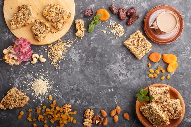 Hausgemachtes müsli aus haferflocken, datteln, getrockneten aprikosen, rosinen, nüssen mit einer tasse kaffee. draufsicht, rahmenhintergrund