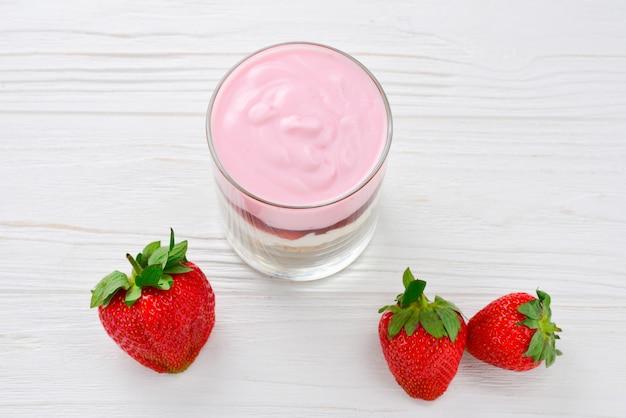 Hausgemachtes müsli-frühstück mit erdbeeren und joghurt, serviert im glas.