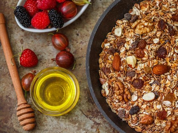 Hausgemachtes müsli mit rosinen, walnüssen, mandeln und haselnüssen. müsli und honig