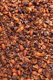 Hausgemachtes müsli, müsli mit stücken dunkler schokolade, mandeln und haselnüssen. draufsicht