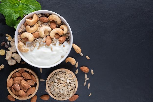 Hausgemachtes müsli oder müsli, schüssel hafergranola mit joghurt, mandeln, cashewnüssen, minze und nüssen auf dem schwarzen felsenbrett für gesundes frühstück, kopienraum. gesundes frühstücksmenükonzept.
