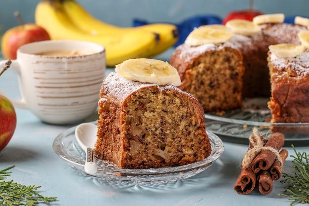 Hausgemachtes muffin mit äpfeln, bananen und zimt, bestreut mit puderzucker auf hellblau und einer tasse kaffee