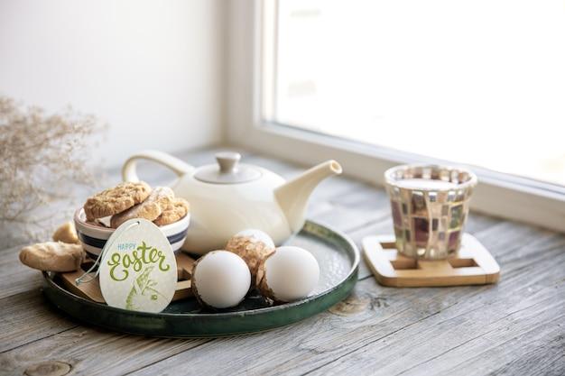 Hausgemachtes osterstillleben mit tee und keksen auf der fensterbank am morgen