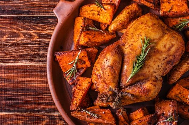 Hausgemachtes paprika-kräuter-ganzes huhn mit gewürzen süßkartoffel.