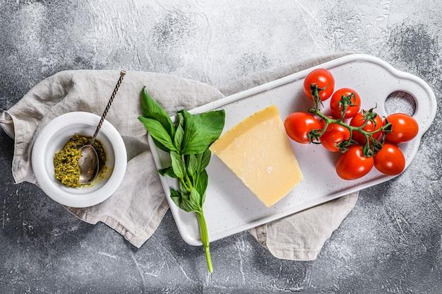Hausgemachtes pesto in marmormörser, basilikumblättern und parmesan auf einem schneidebrett. platz für text