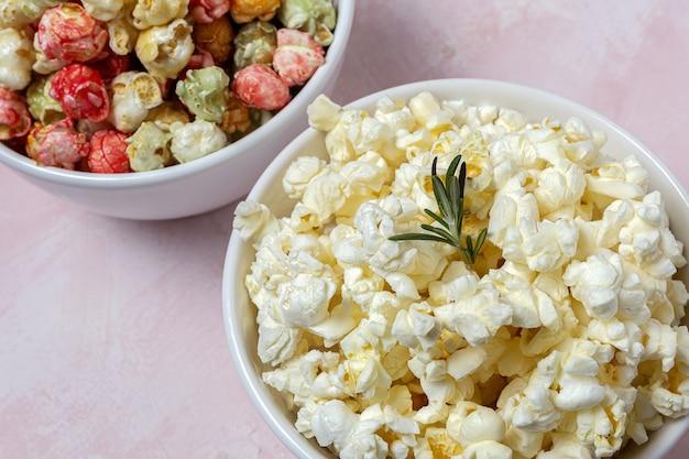 Hausgemachtes popcorn auf farbigem tisch mit kontrastreichem licht. snack-konzept