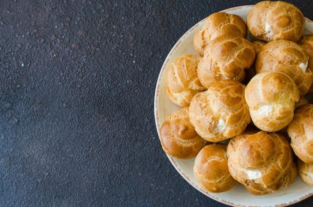Hausgemachtes profitrollengebäck gefüllt mit vanillesoße. eclairs mit sahne, französisches dessert.