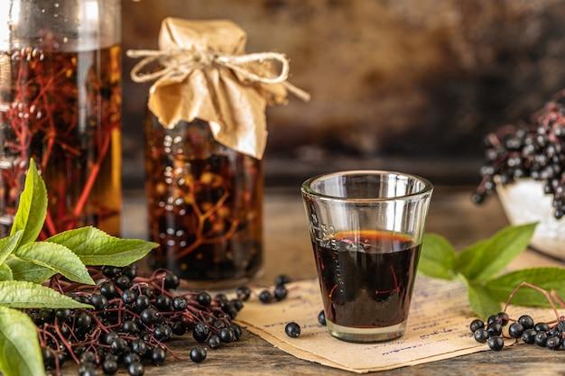 Hausgemachtes rezept für schwarzen holundersirup in einer glasflasche auf einem holztisch. frische beeren im hintergrund. speicherplatz kopieren