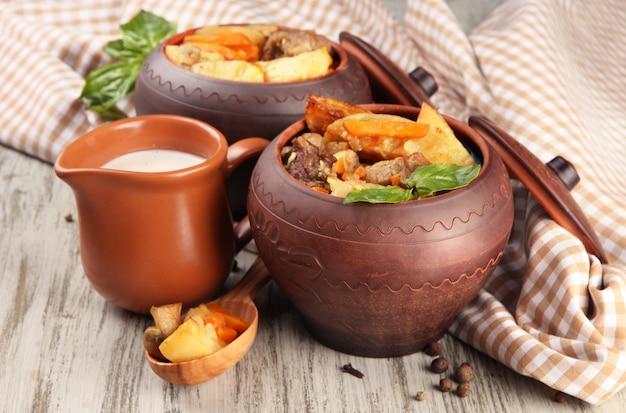 Hausgemachtes rindfleisch unter rühren mit gemüse in töpfen auf holz braten
