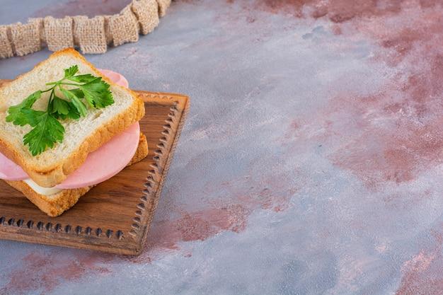 Hausgemachtes sandwich auf einem brett, auf der marmoroberfläche