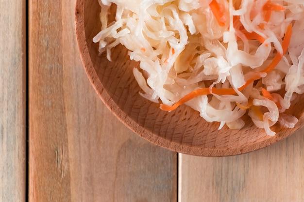 Hausgemachtes sauerkraut auf einem holzteller. fermentierter kohl mit karotte auf hellem hintergrund. öko-lebensmittel, der trend zu gesunder ernährung.