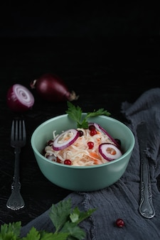 Hausgemachtes sauerkraut mit karotten mit kräutern auf schwarzem hintergrund. eingelegter kohl auf dem teller mit sackleinen auf dem holztisch. das konzept der konserven. vegetarisches essen.