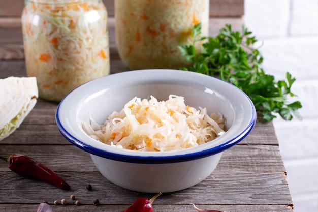 Hausgemachtes sauerkraut mit karotten und gewürzen auf teller, saurer weißkohl