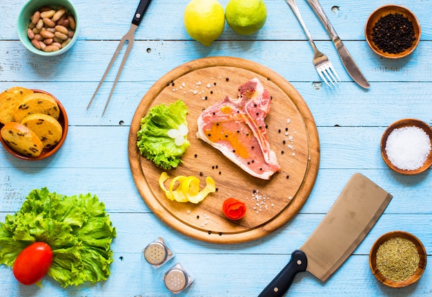 Hausgemachtes schweinefleischsteak mit gewürzen, blattsalat auf holzbrett und teller,