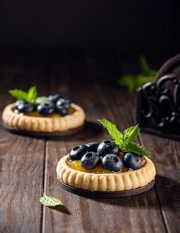 Hausgemachtes shortbread-törtchen mit zitronenquark und frischen blaubeeren auf alter dunkler holzoberfläche. holiday food-konzept mit kopierraum