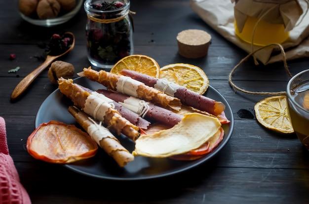 Hausgemachtes sortiertes fruchtleder und getrocknete chips im teller auf holztisch mit kräutertee