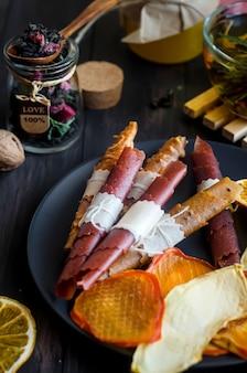 Hausgemachtes sortiertes fruchtleder und getrocknete chips im teller auf holztisch