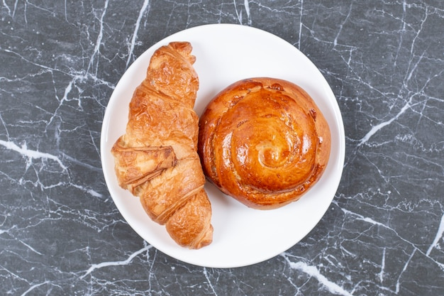 Hausgemachtes süßes brötchen und croissant auf dem teller, auf der marmoroberfläche