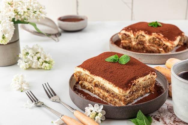 Hausgemachtes traditionelles italienisches dessert tiramisu in einem teller mit kaffeetasse, dessertgabeln und blumen auf weißer oberfläche für leckeres frühstück