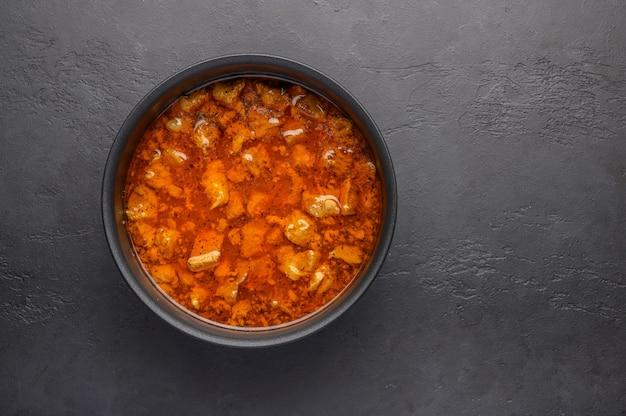 Hausgemachtes traditionelles ungarisches gulaschgericht in einem topf vor einem dunklen hintergrund.
