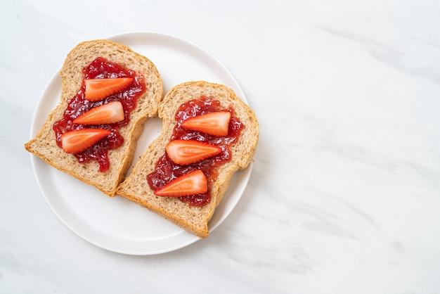 Hausgemachtes vollkornbrot mit erdbeermarmelade und frischer erdbeere
