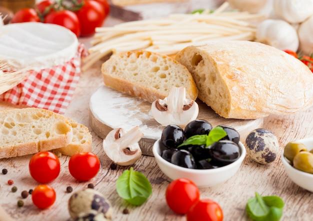 Hausgemachtes weizenbrot mit wachteleiern und rohem weizen und frischen tomaten. klassisches italienisches dorfessen. knoblauch, schwarze und grüne oliven. holzspatel