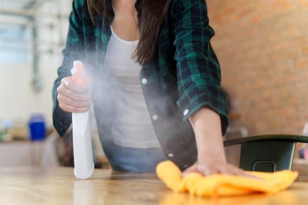 Haushälterin besprüht und wischt tabelle unter verwendung eines orange gewebes ab.