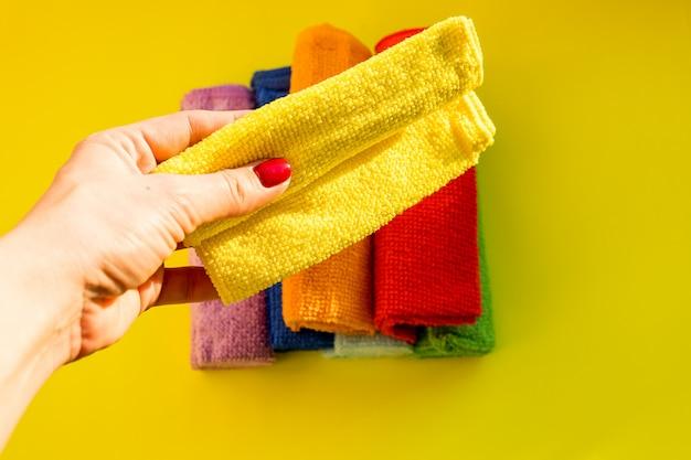 Haushälterin hält ein reinigendes trockenes mikrofasertuch. reinigungs- oder reinigungskonzepthintergrund. regelmäßige reinigung. gewerbliches reinigungsunternehmenskonzept. kopierfläche