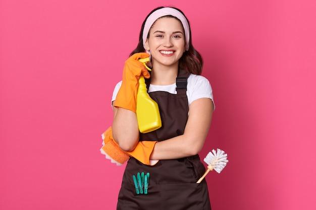 Haushälterin hält flasche mit sauberer flüssigkeit in händen