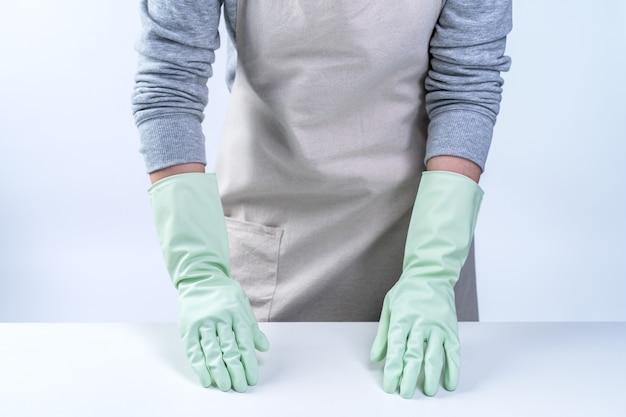 Haushälterin in schürze mit grünen handschuhen